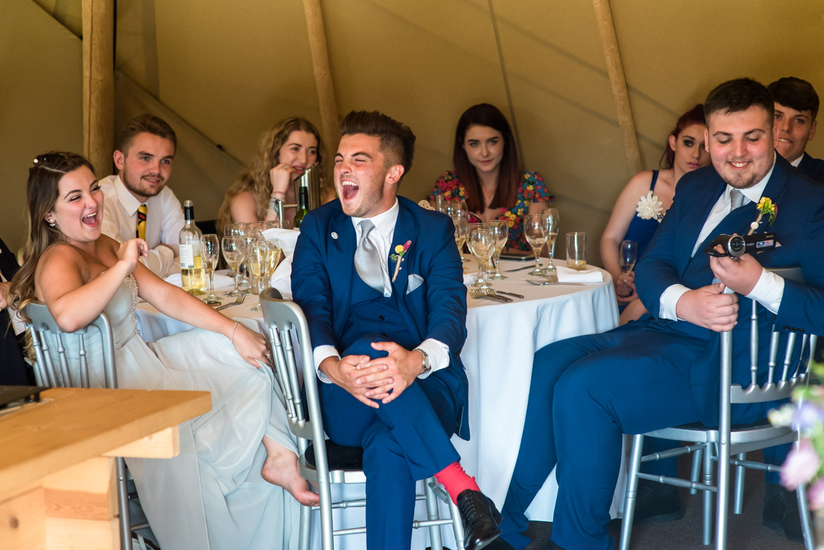 Family of the bride and groom photographed laughing at wedding speeches