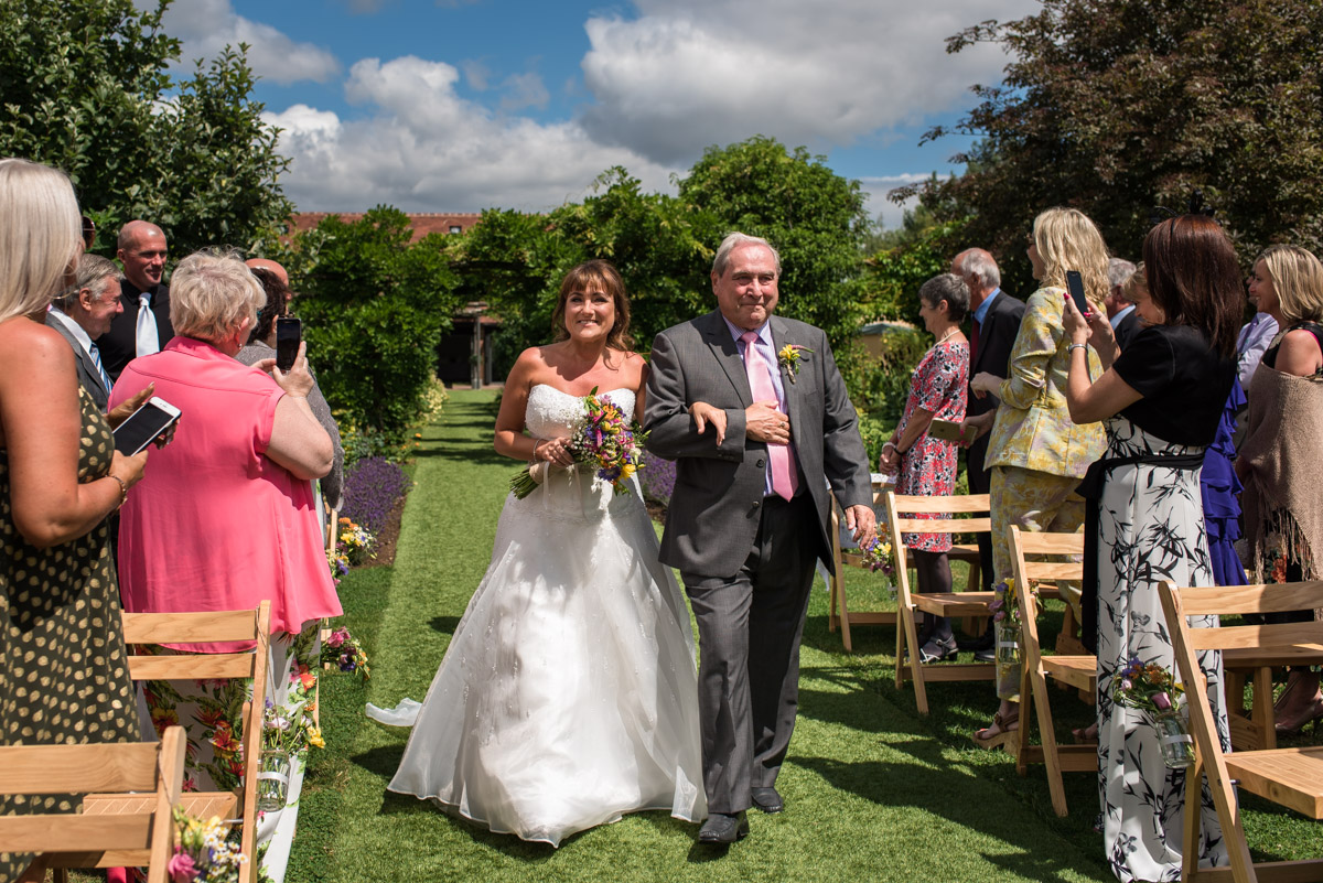 The Gardens Yalding wedding photography. Debbie being walked down the aisle by her father