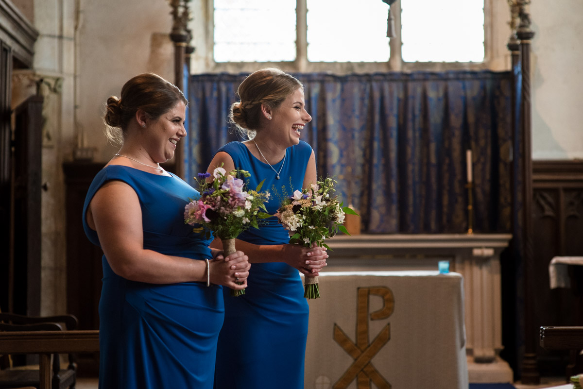 Photograph of bridesmaids laughing during church wedding