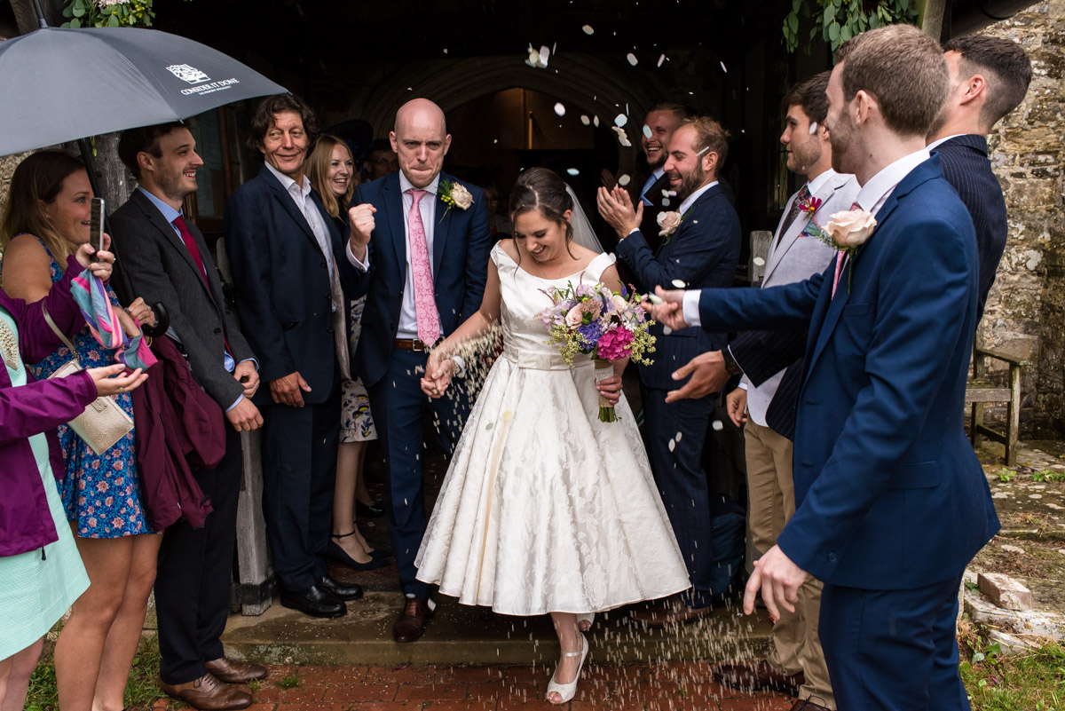 Photograph of Emily and Tom leaving the church under confetti after their wedding ceremony