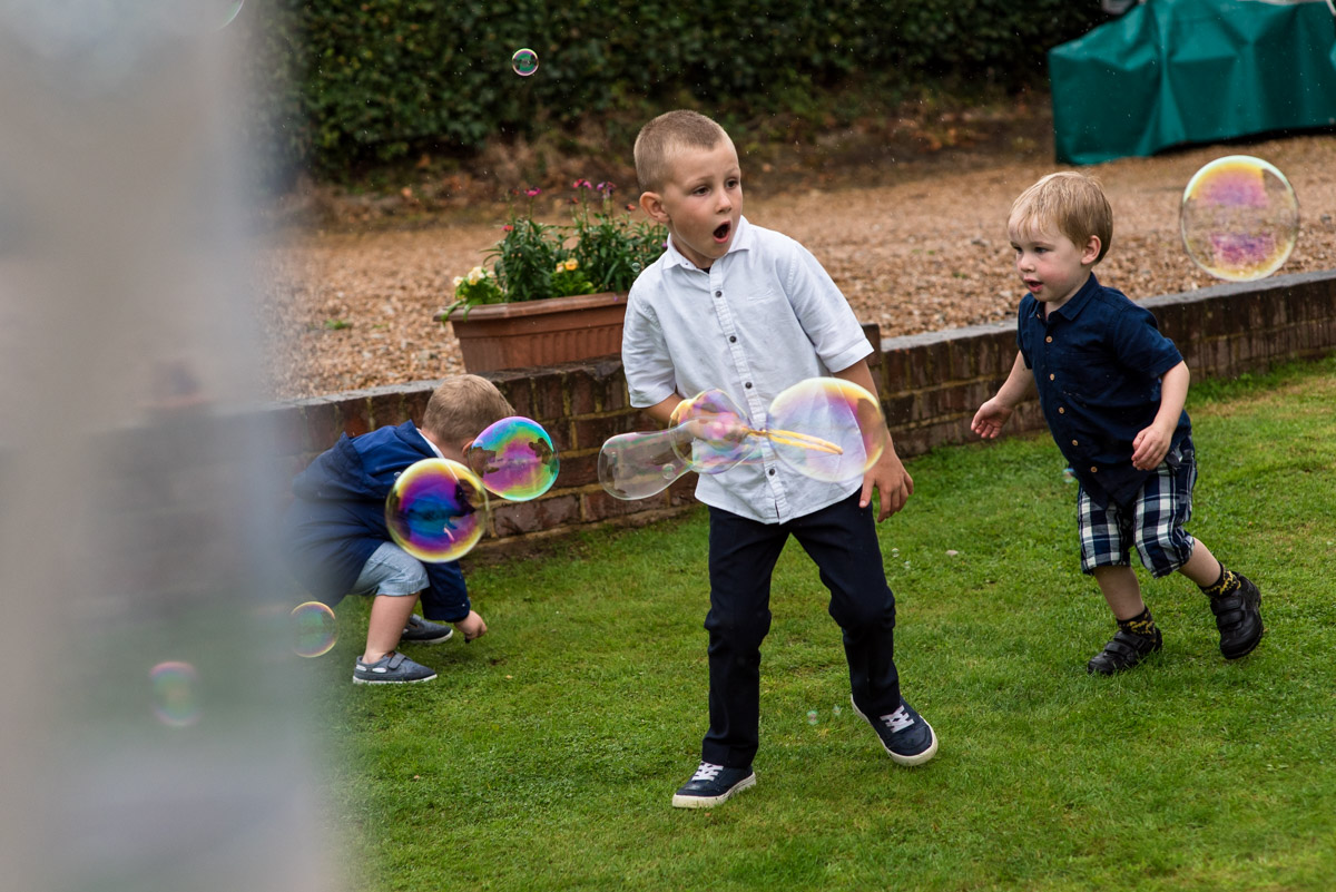 Boys playing with bubbles at emily and Toms east sussex wedding