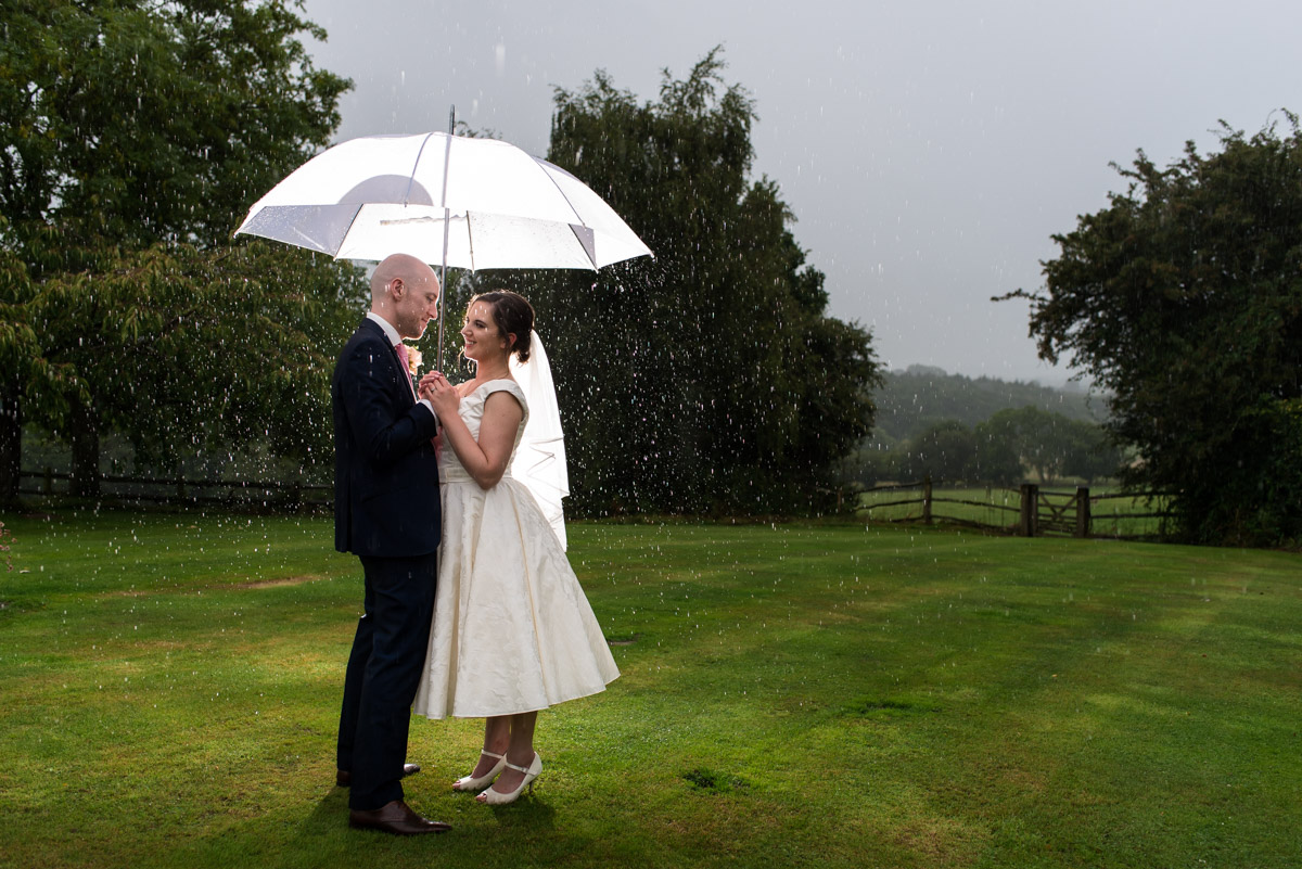 Photograph of Emily and Tom in the rain on their wedding day