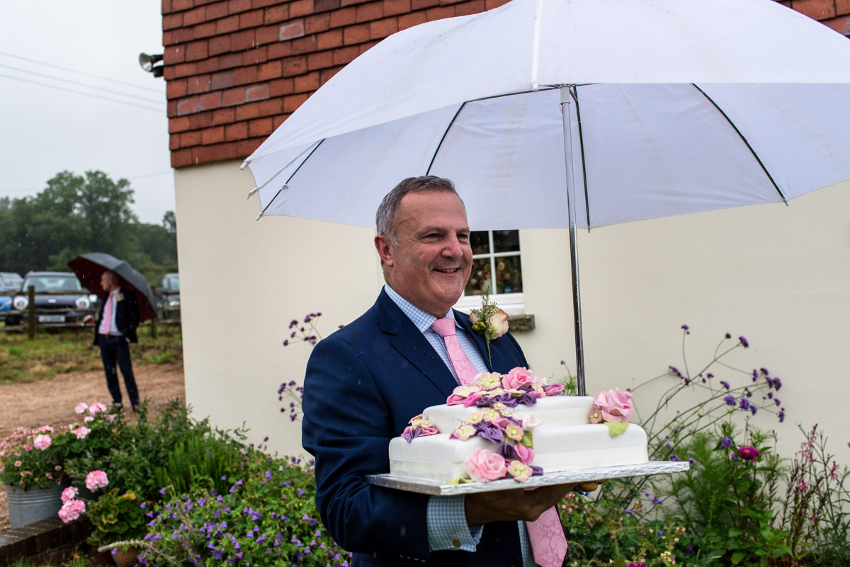 East sussex wedding photography, Emily's dad carrying wedding cake
