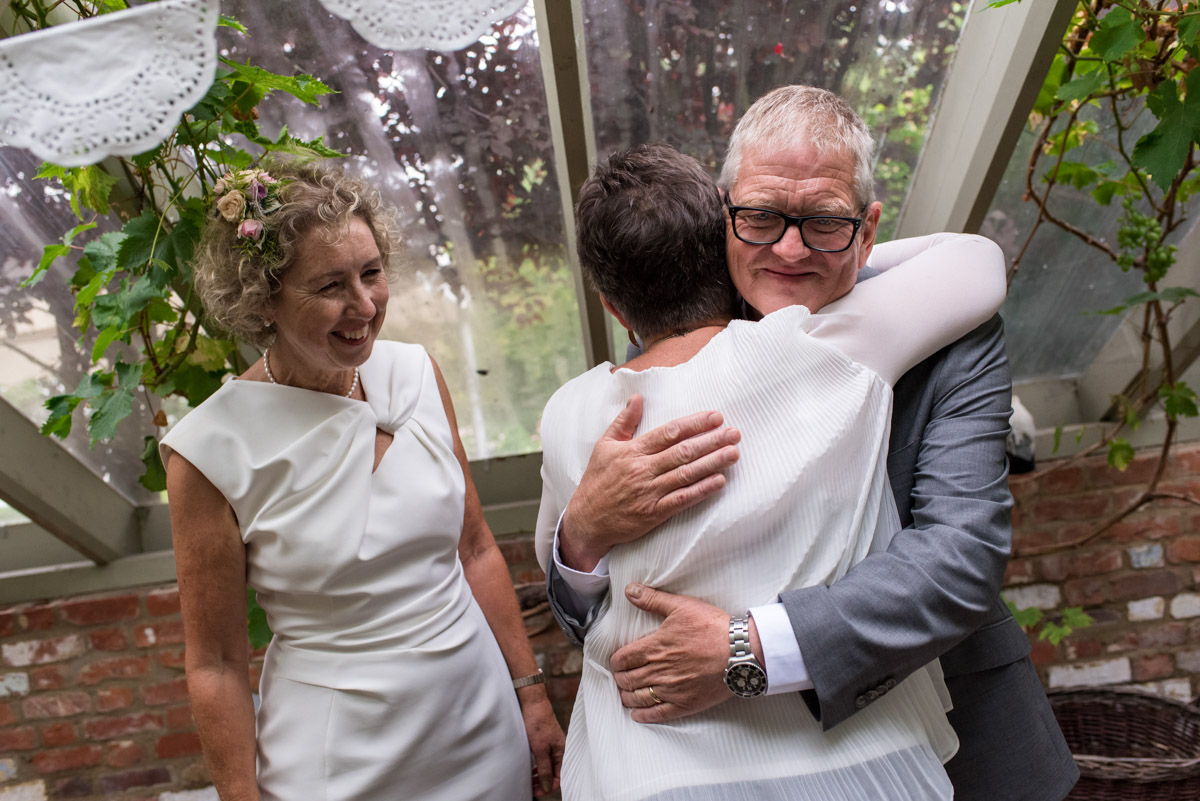 John is photographed hugging wedding guest after ceremony