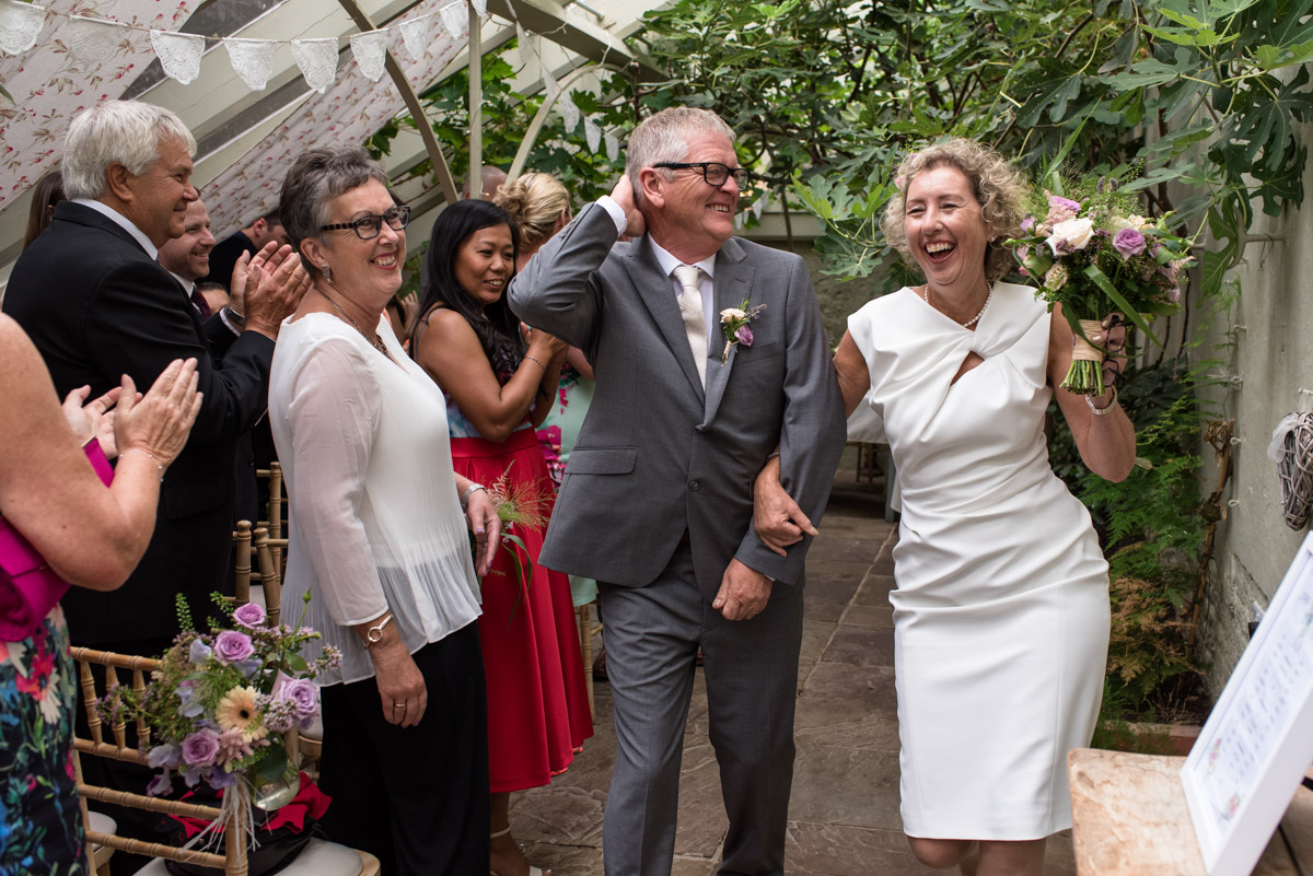 The Secret garden wedding photography of Kate and John dancing down the aisle