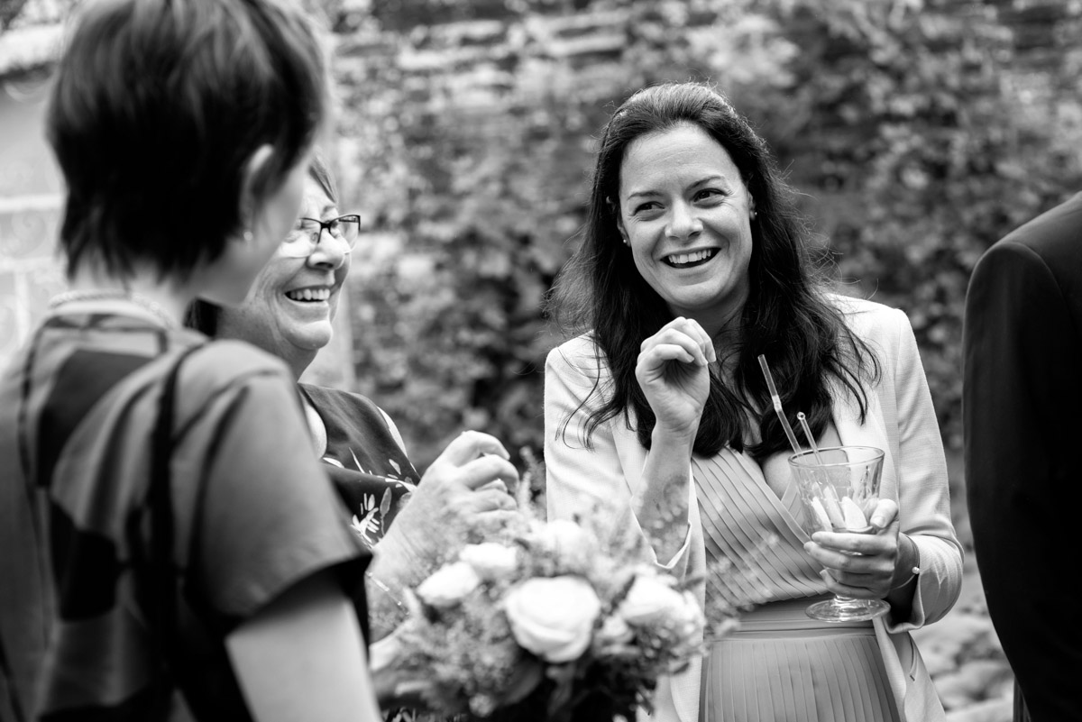 Wedding guests photographed having drinks at the secret garden in Kent