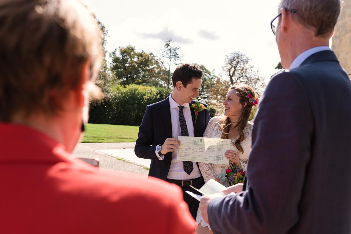 Photograph of james and Alex holding wedding certificate after their danson House wedding ceremony