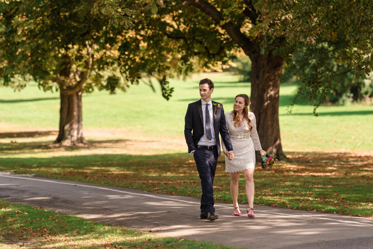 Alex and James are photographed in the park walking hand in hand