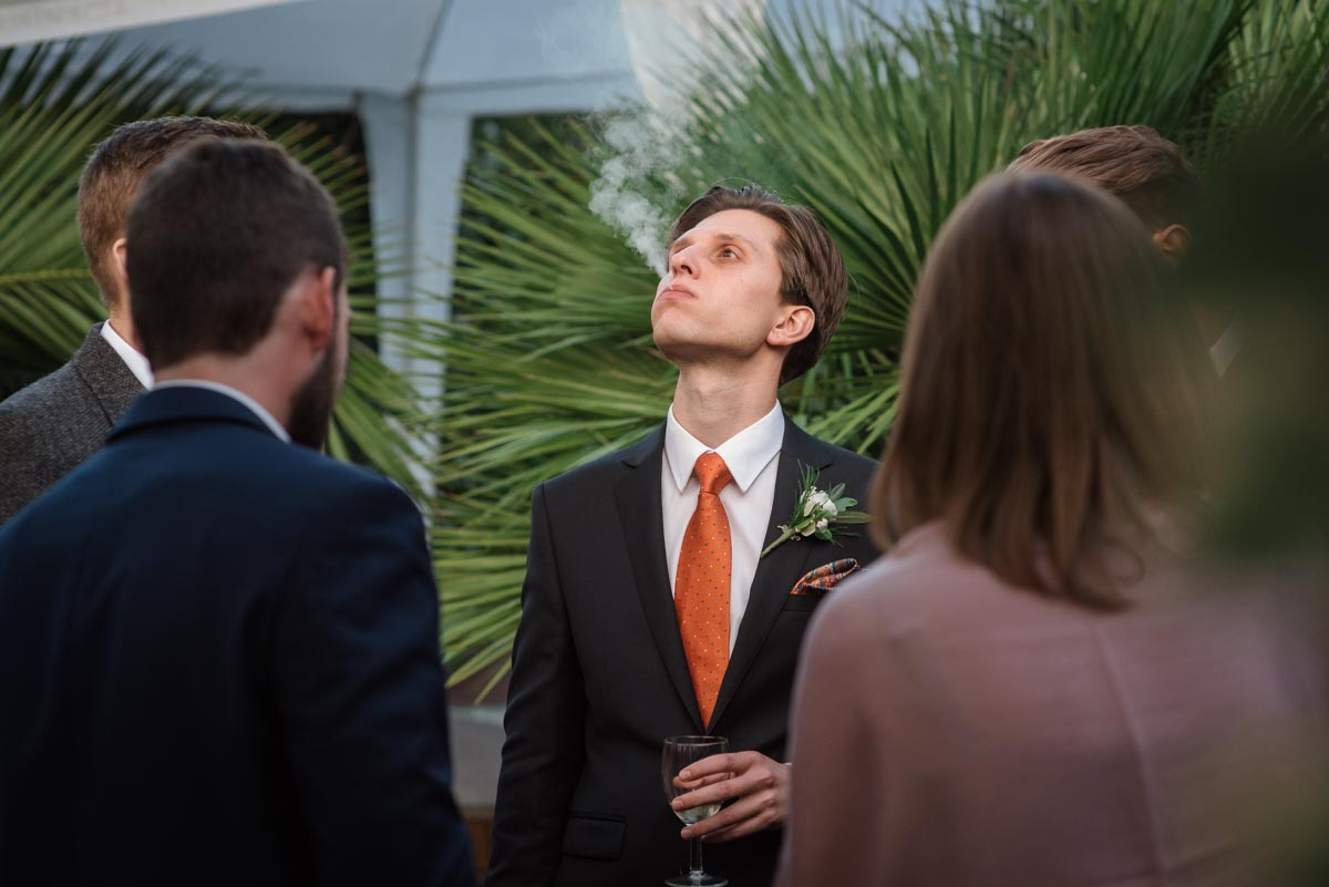 Best man photographed blowing cigar smoke