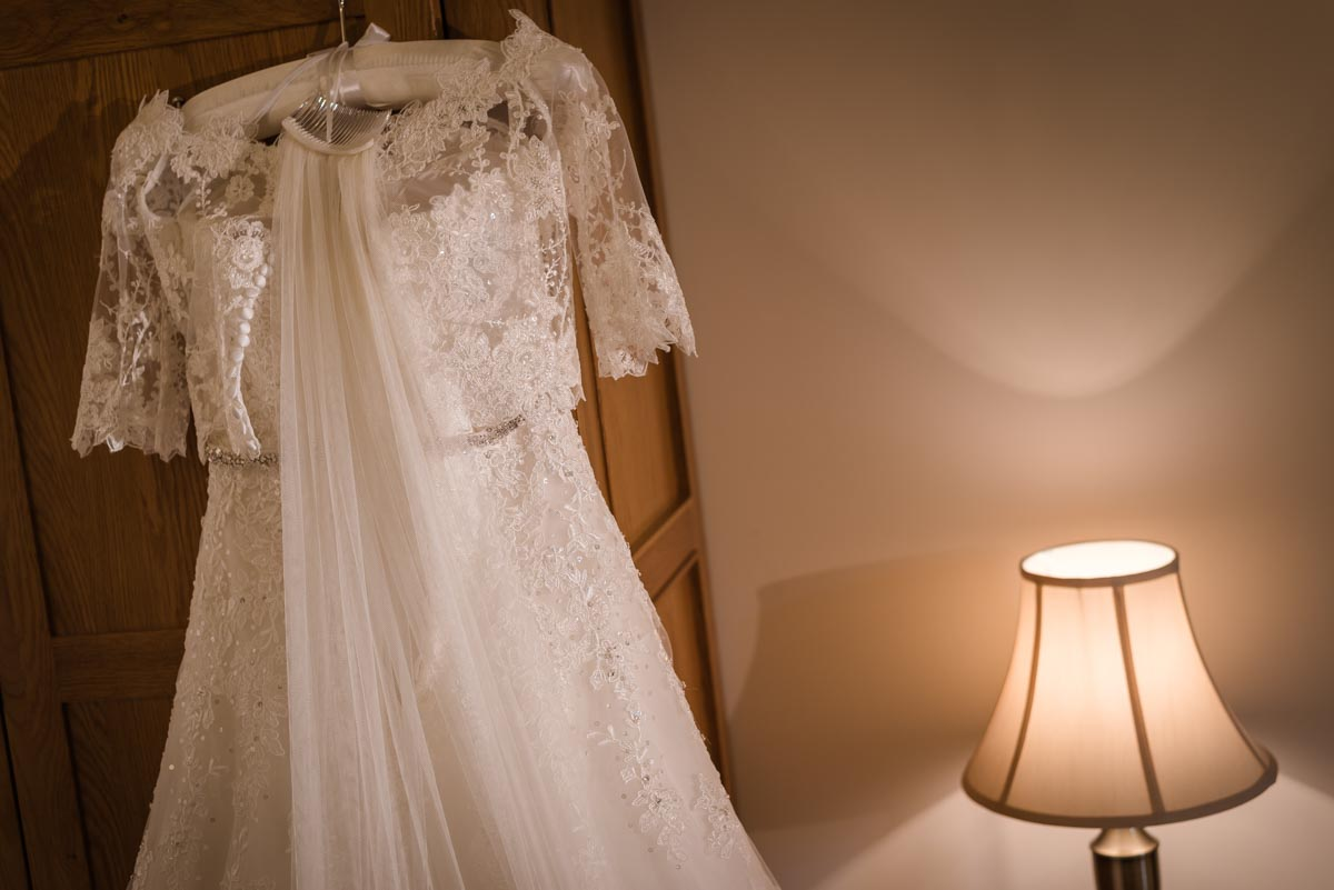 Photograph of Rebecca's wedding dress hanging in room at darling Buds farm