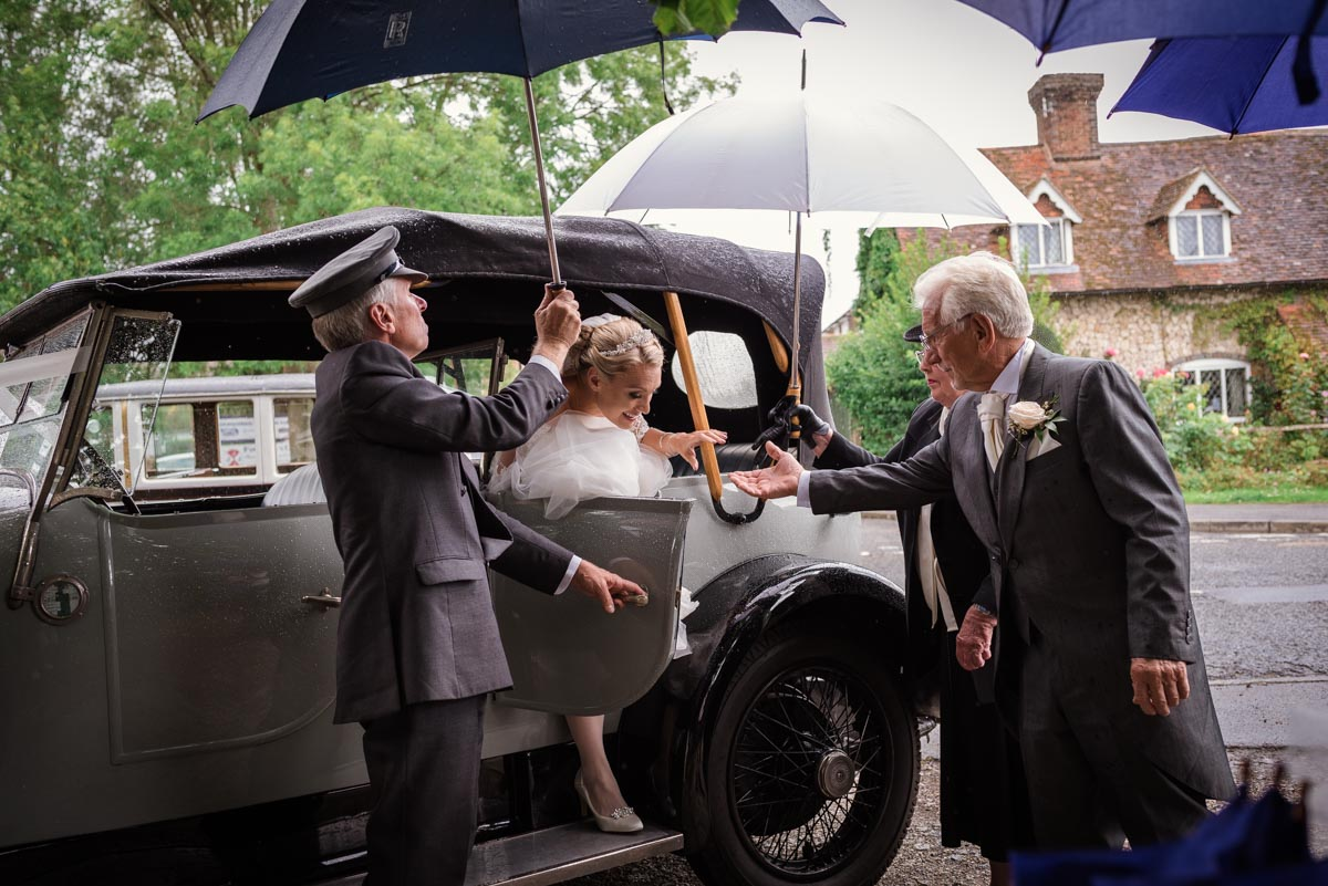 Rebecca is helped out of wedding car by her father