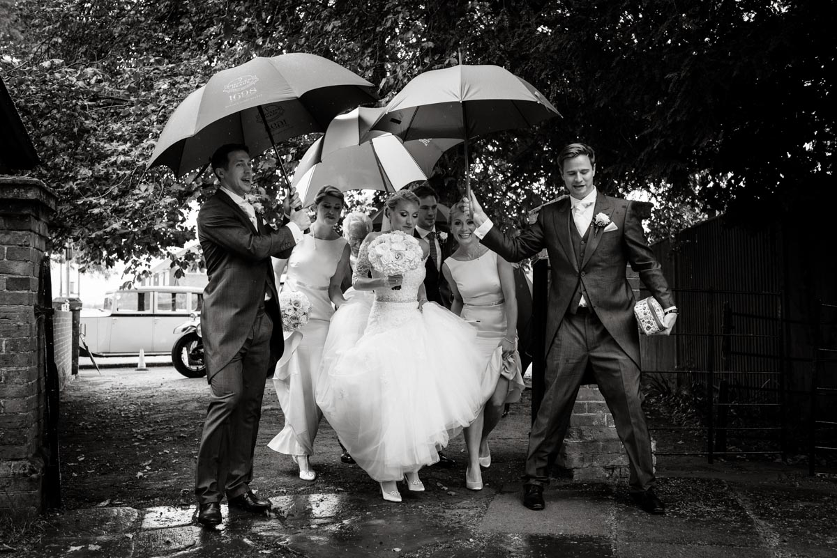 Photograph of Rebecca arriving for her Smarten church wedding in Kent being sheltered from the rain