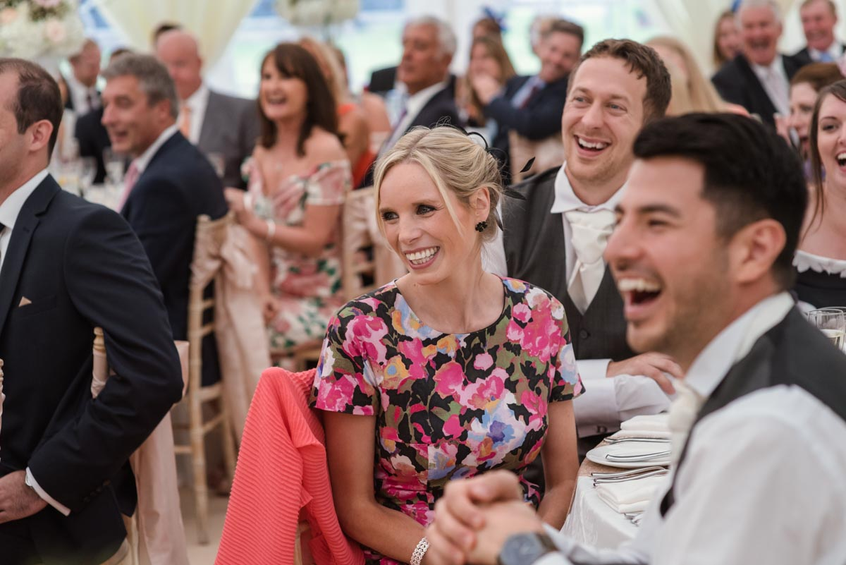Photograph of guests laughing during wedding speeches in Kent