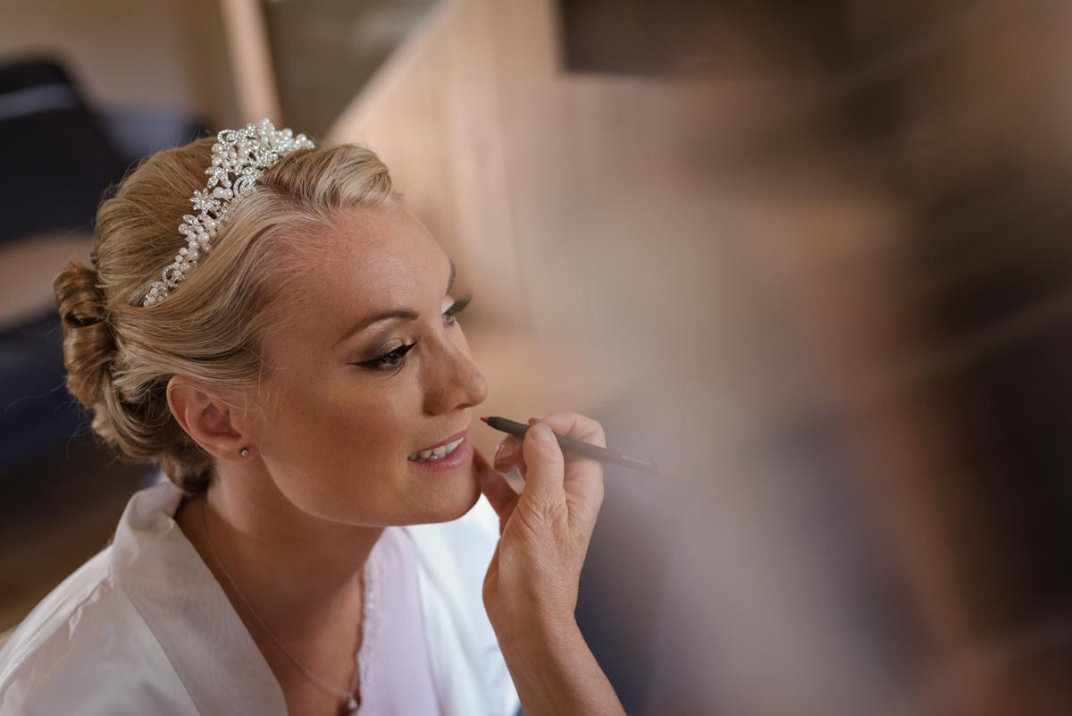 Rebecca is photographed having her make up done on her wedding day in Kent