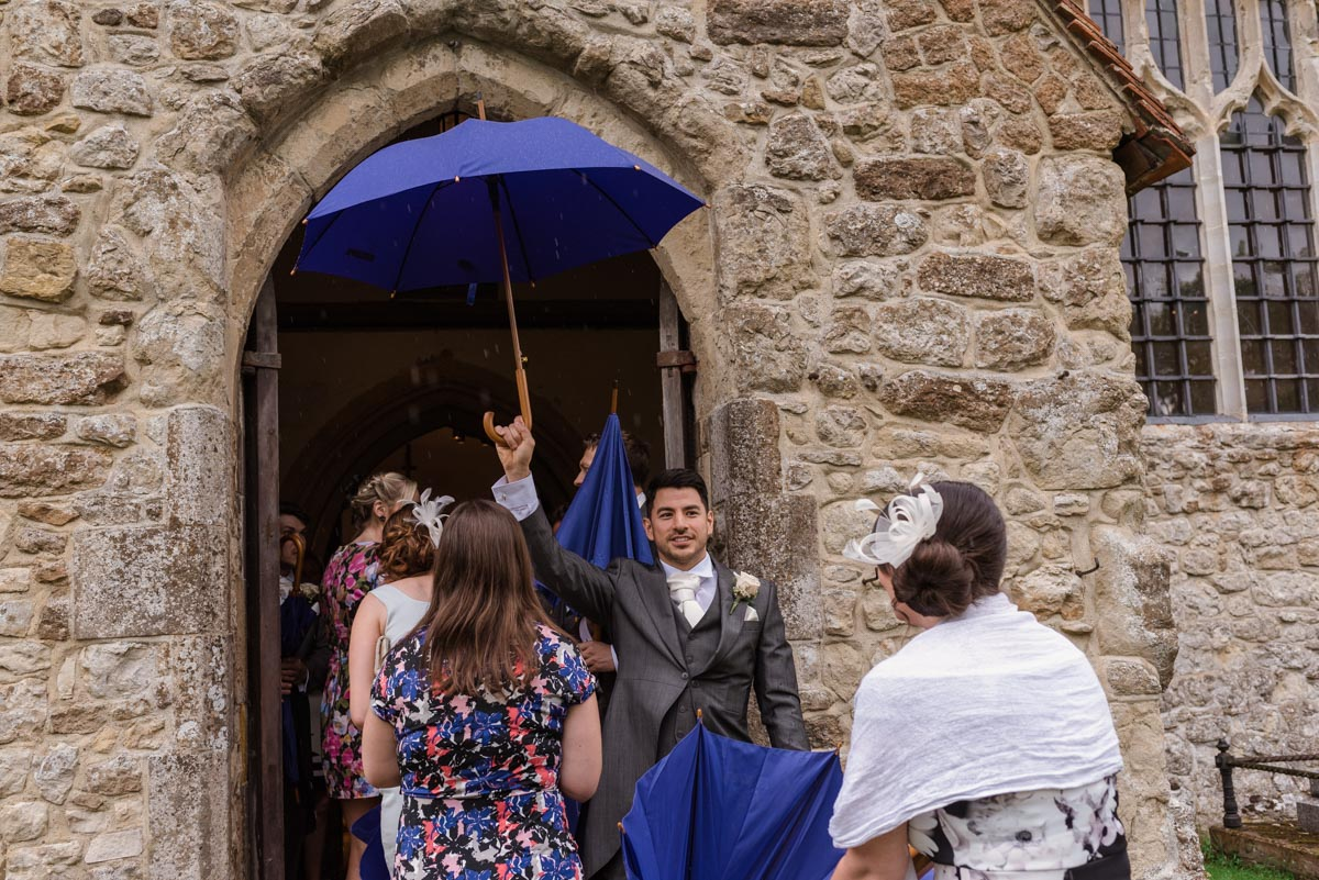 Photograph of usher with umbrella at wedding in Kent