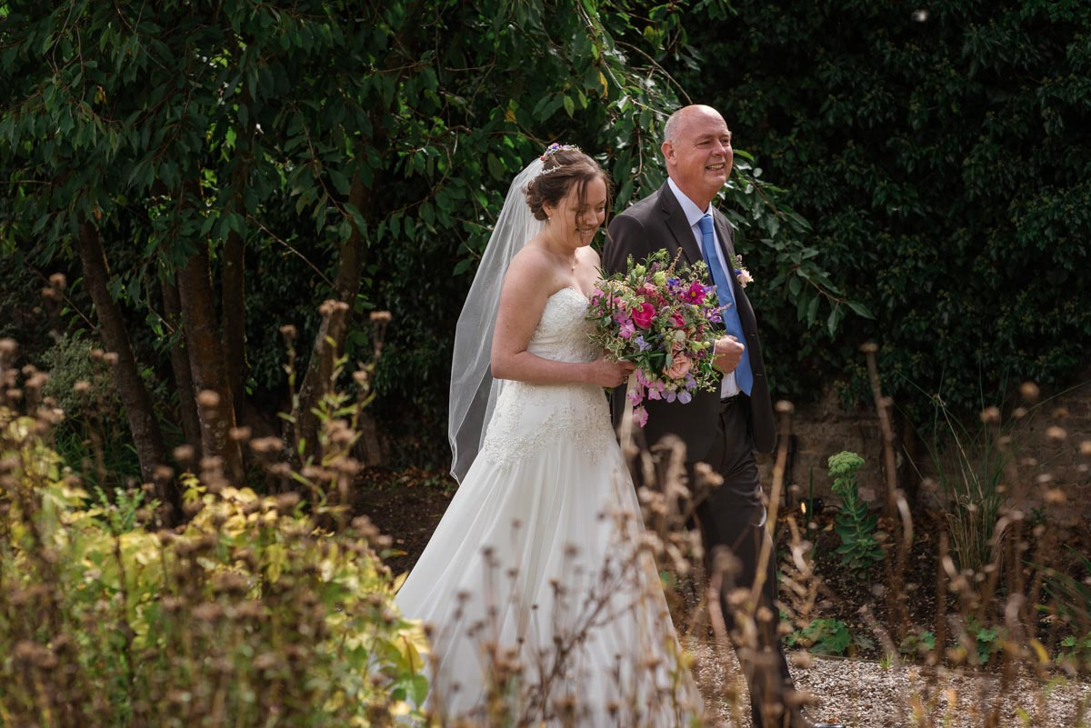sarah is escorted to her Secret Garden wedding by her dad