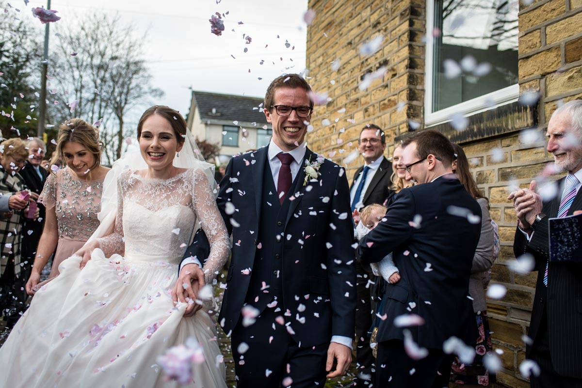 Katherine and Tom are photographed having confetti thrown on them after their Yorkshire wedding
