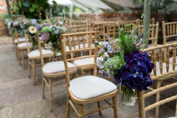 Summer garden flowers in jam jars at wedding at The Secret garden wedding venue