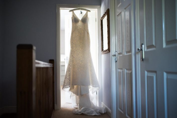 Lace long wedding dress photographed hanging from door frame