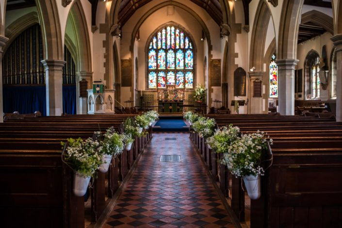 Flowers in ornate buckets decorate church pies for wedding