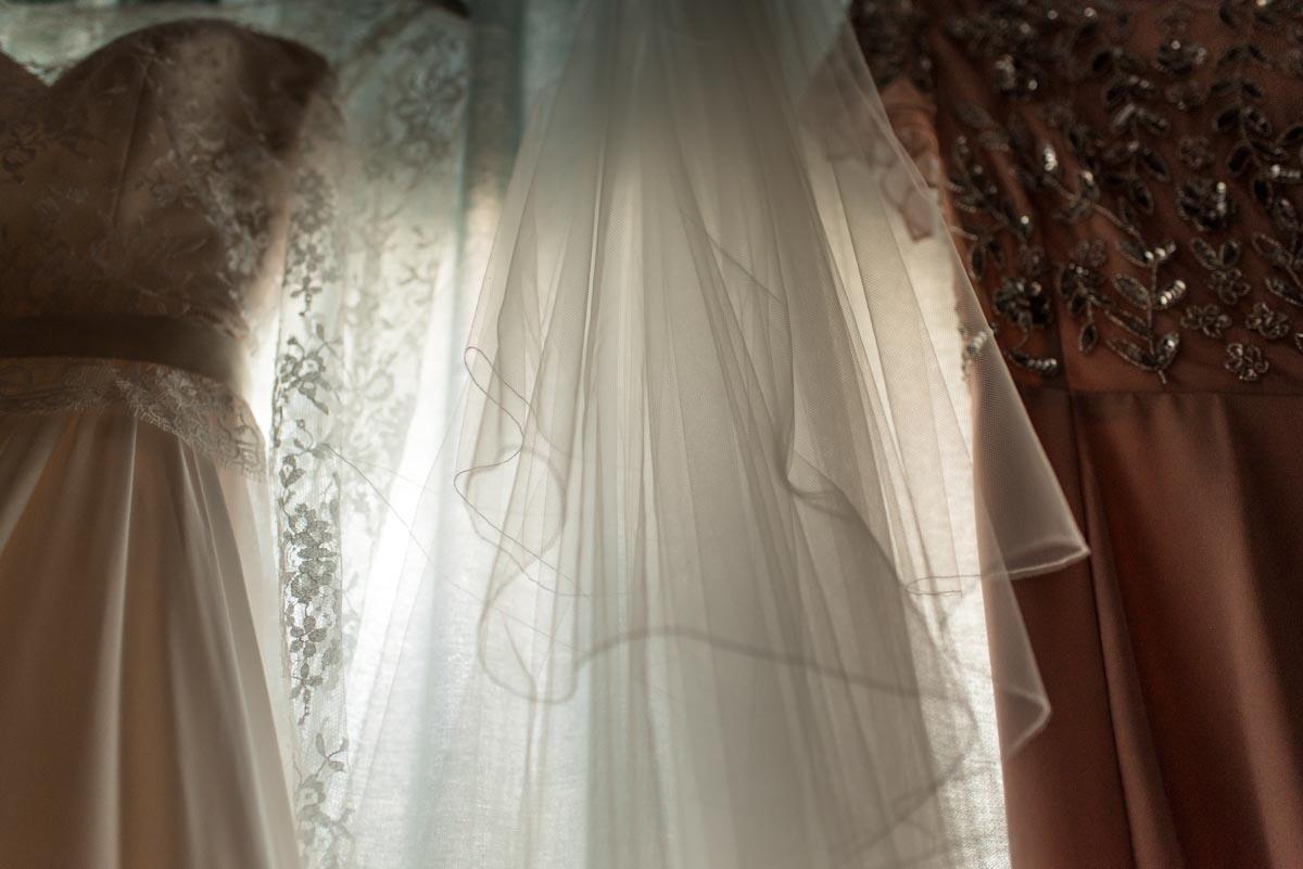 Katherines wedding dress hangs from window frame