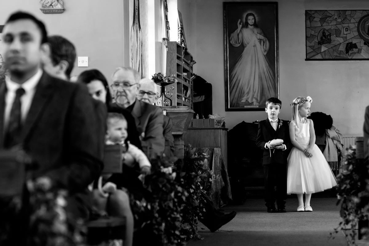 page boy and flower girl photographed waiting in church for brides arrival