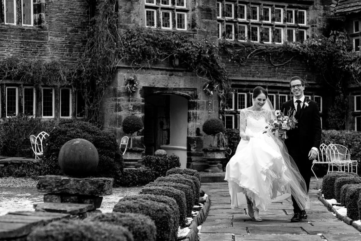 Tom and Katherine photographed walking down path outside Holdsworth House on their wedding day