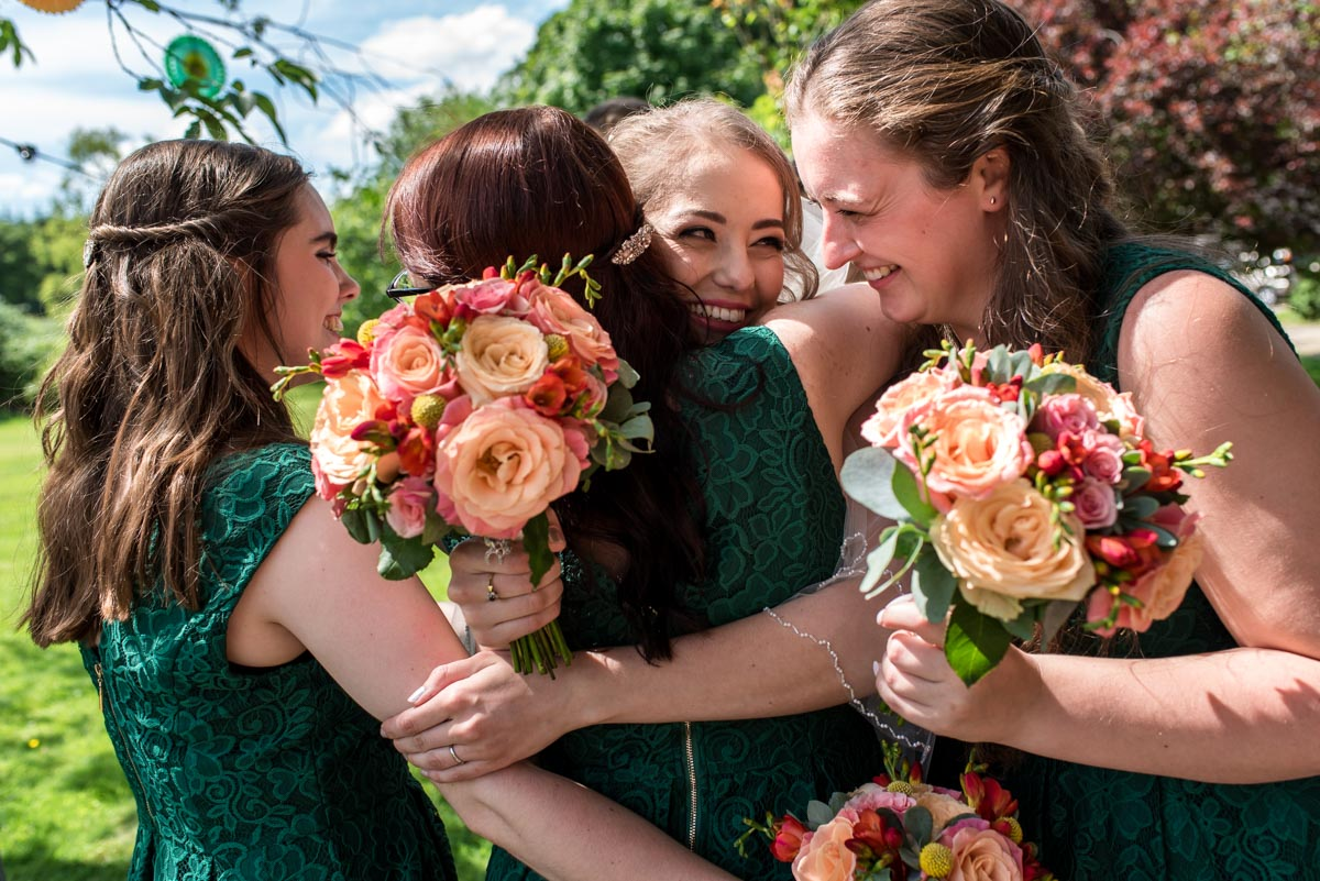 bride receives hugs of congratulations from bridesmaids