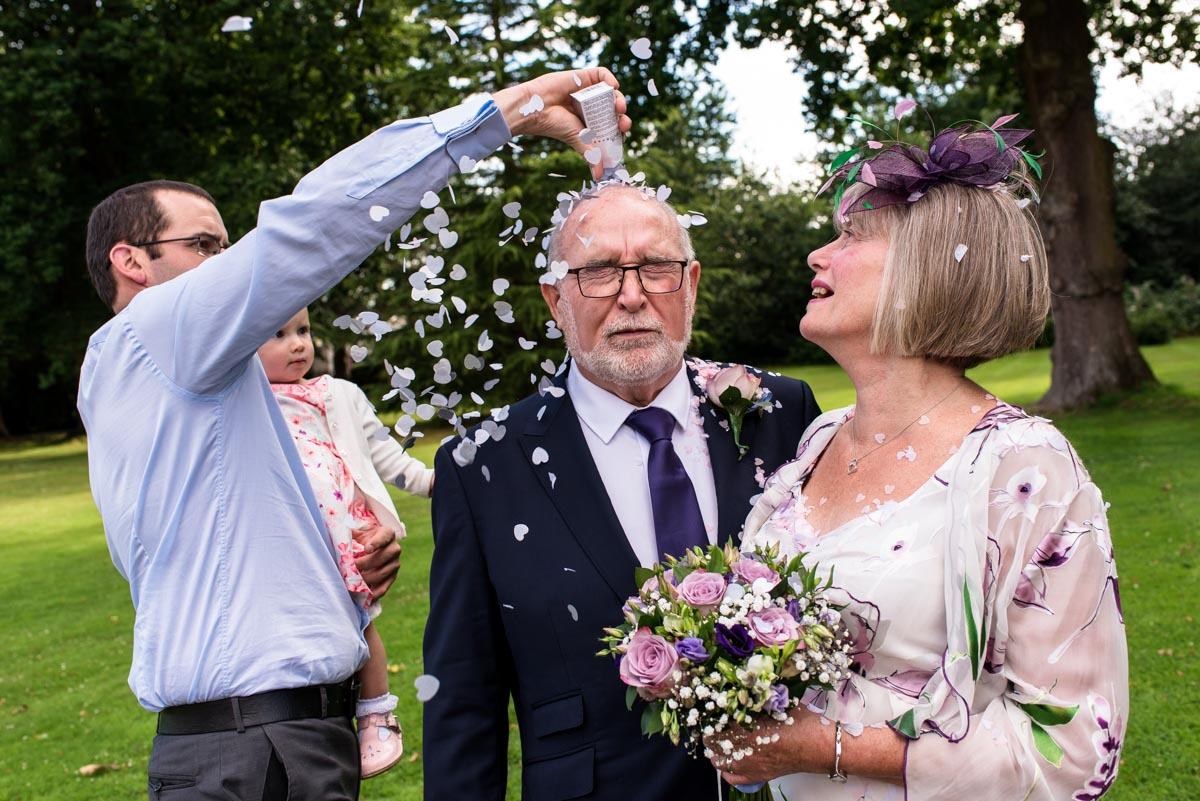Confetti thrown on grooms head after ceremony