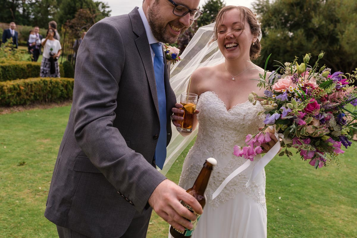 Couple enjoying a drink after their wedding ceremony at the secret garden in Kent