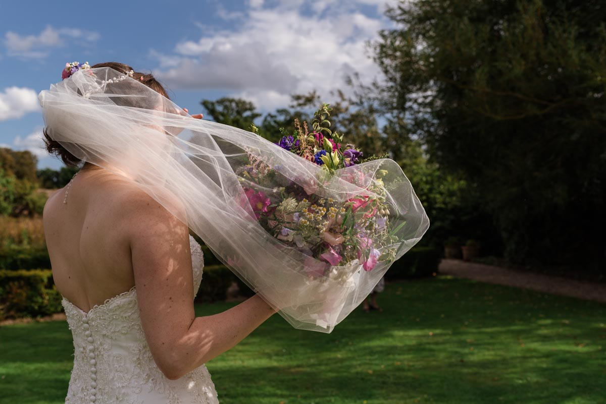 Photograph of veil covering wedding bouquet at secret garden wedding in Kent