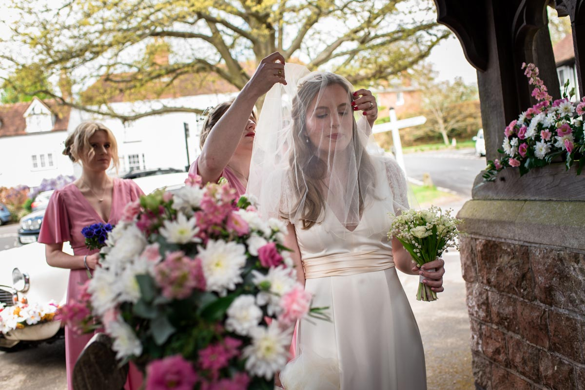 Bridesmaid places veil over brides face before her walk into the church