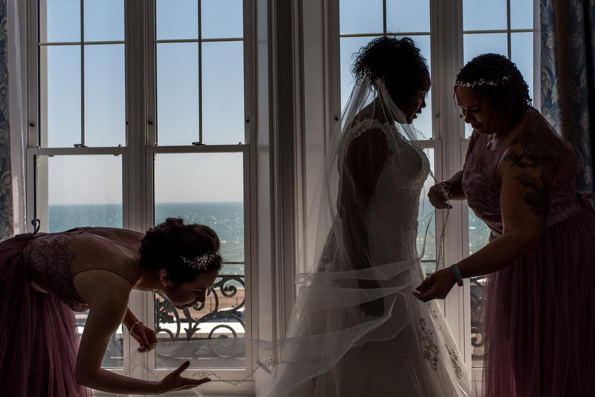 bridesmaids attend to brides veil before her wedding at Hythe Imperial Hotle in kent