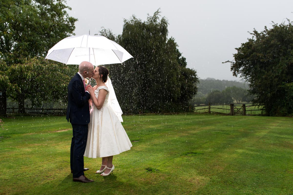 Photograph of wedding couple in the rain