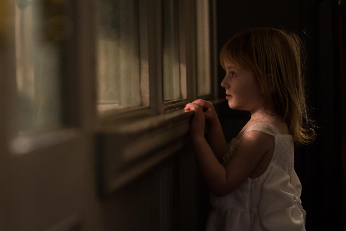 Chilston park hotel wedding photography, little bridesmaid peering through window