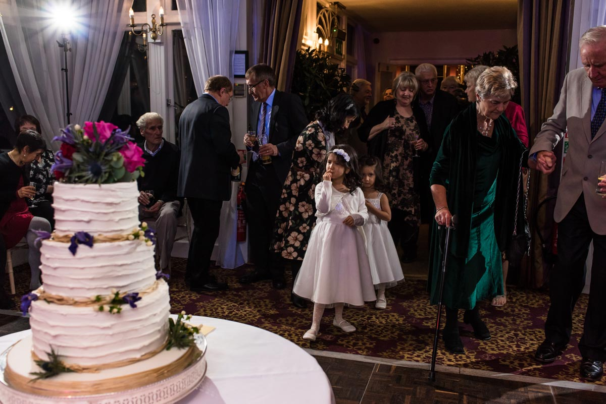 Photograph of flower girls admiring wedidng cake at chilston park hotel in Kent