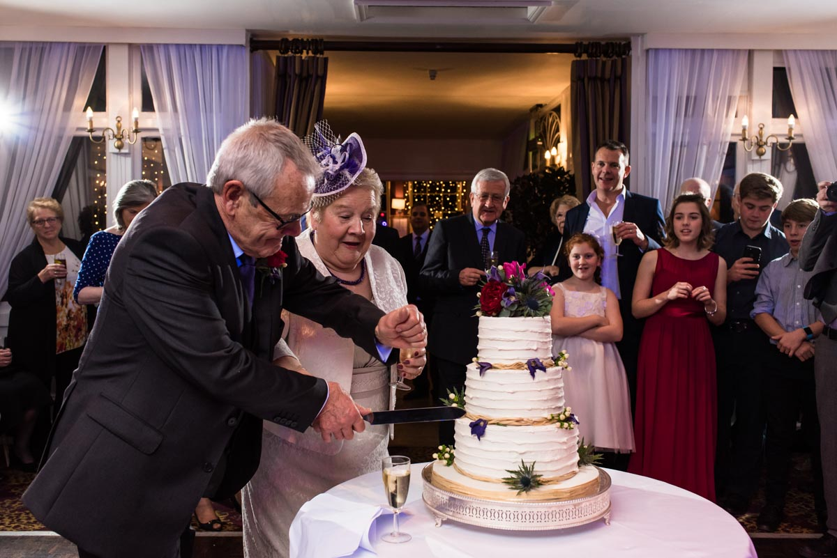 Photograph of Jo and Graham cutting their wedding cake at Chilston park hotel in Kent