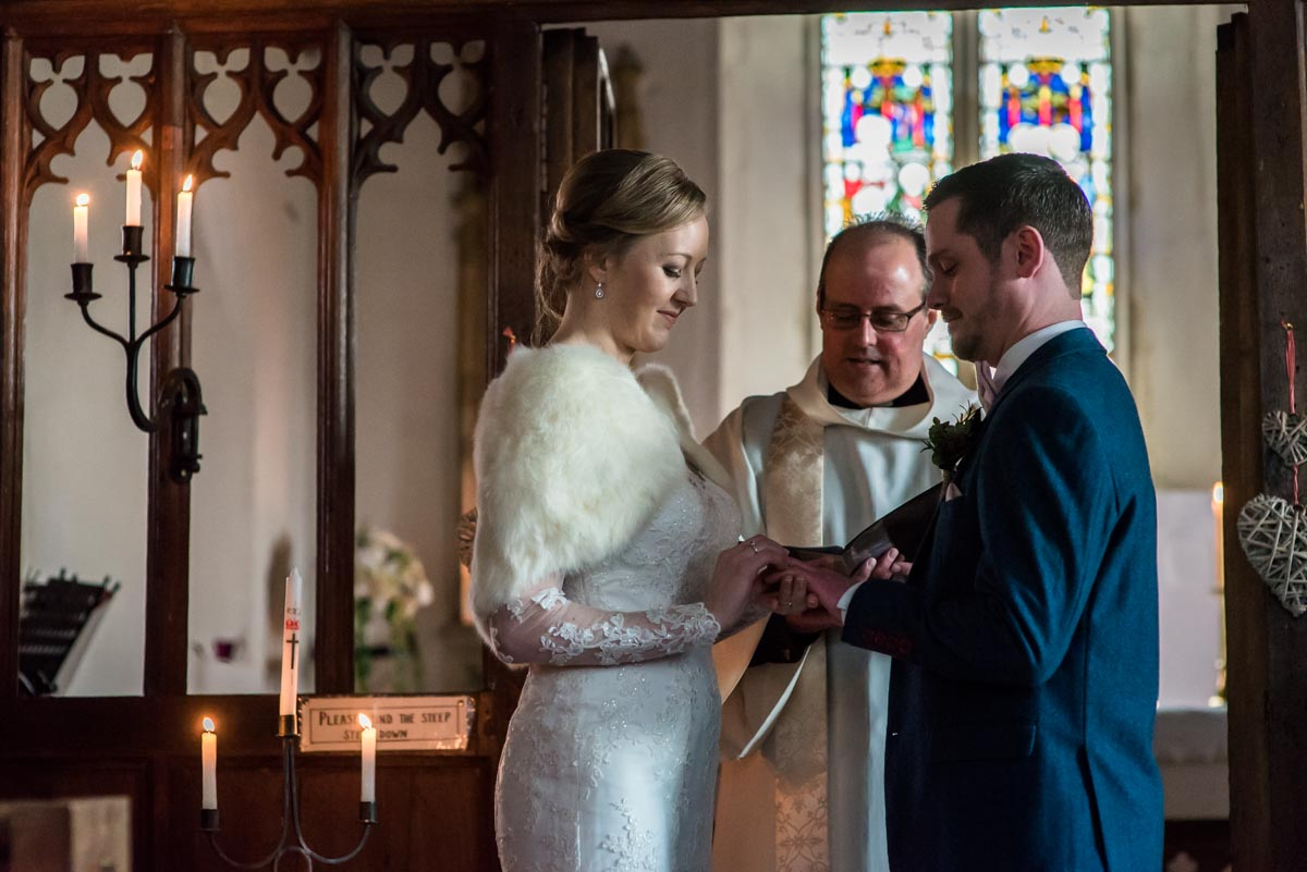 Rebecca is photographed putting wedding ring on Stephens finger during Kent church ceremony