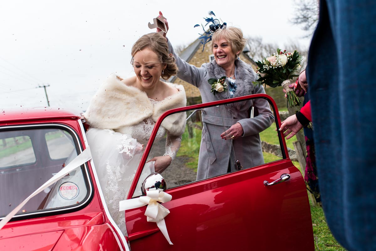 Rebecca is photographed having confetti thrown on her getting into wedding car