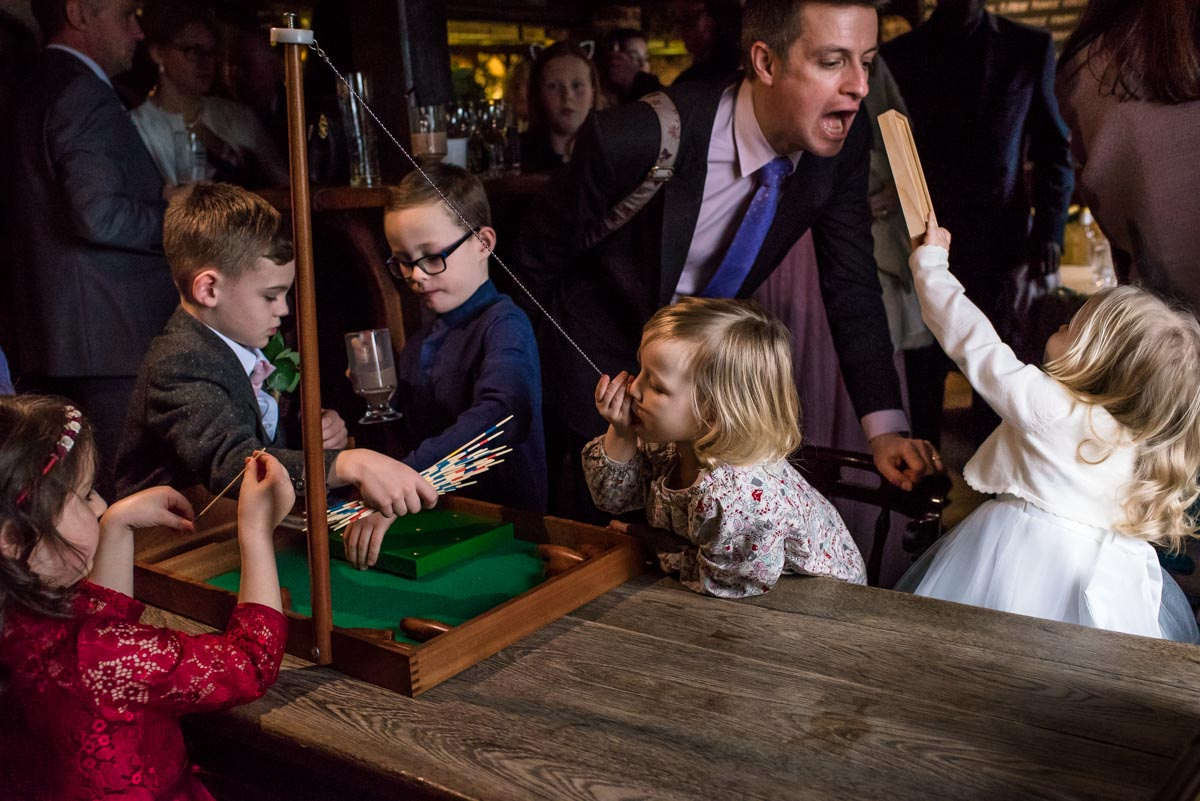 Wedding guests and children play indoor games at Stephen and Rebeccas Ferry House Inn wedding reception