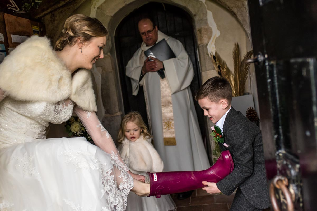 Wedding photography at church. page boy helps bride take off wellington boots