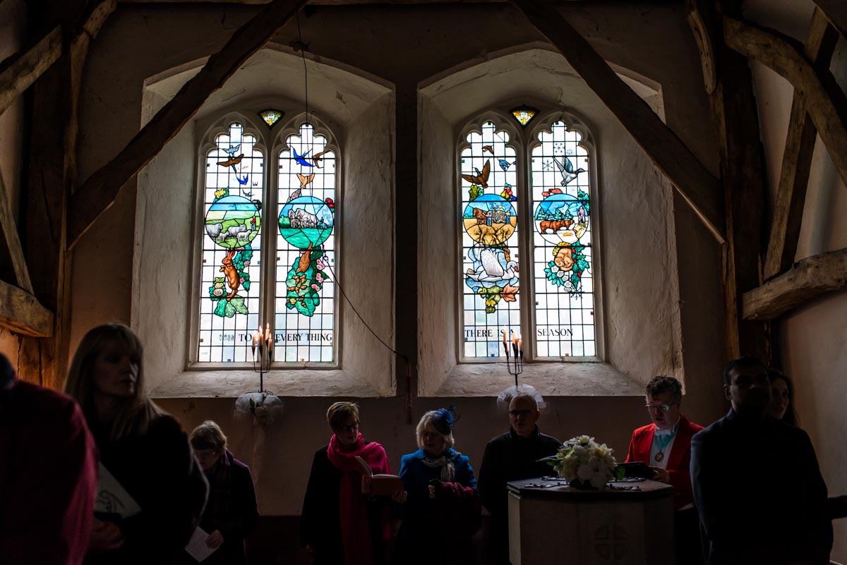 Photograph of wedding guests and stain glass window at St Thomas's church in Kent
