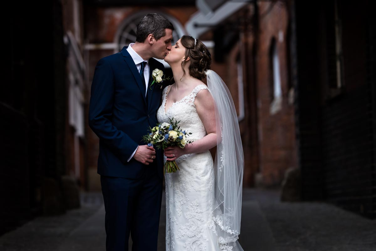 wedding photography portrait of Lindsey and Liam under clock tower at Shepherd Neame brewery