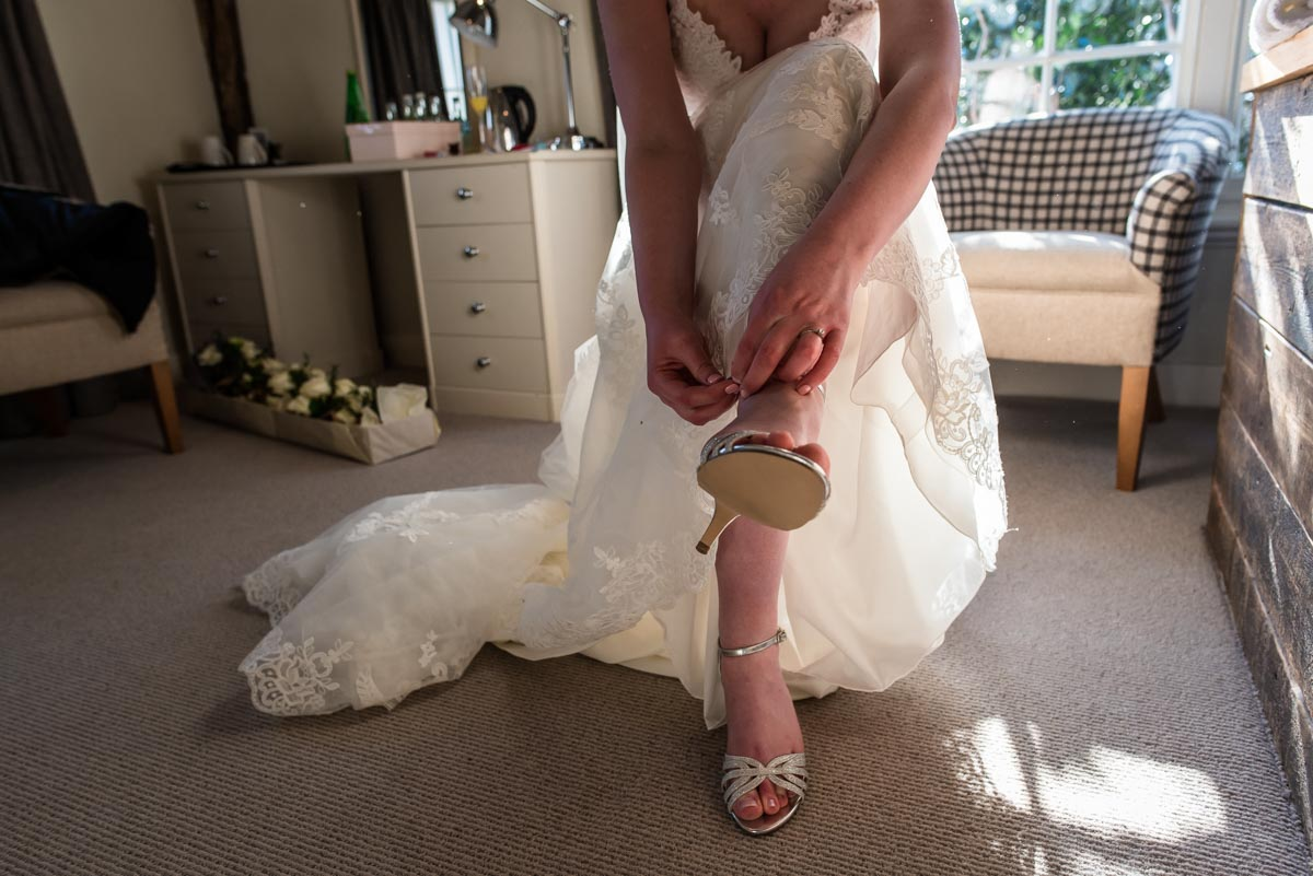 Photograph of Lindsey doing her wedding shoes up