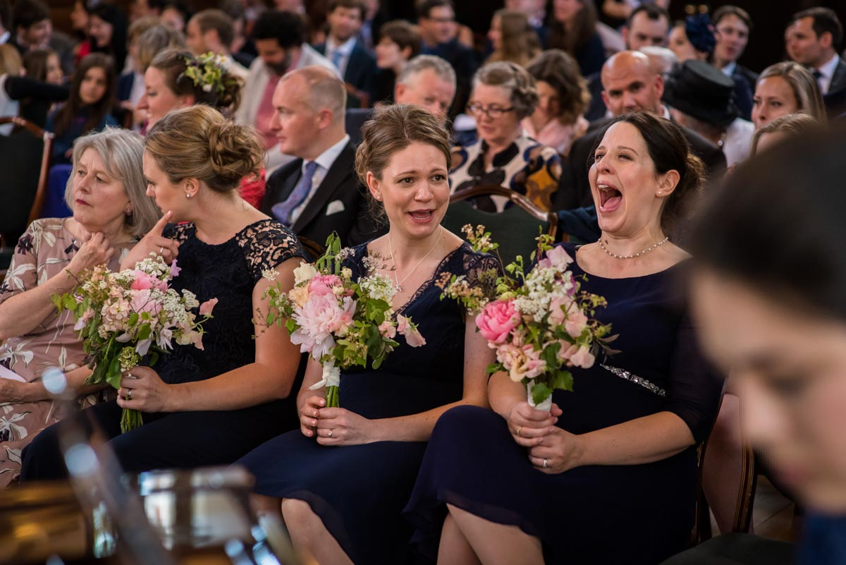 Bridesmaids laughing during wedding ceremony at Grays Inn, London
