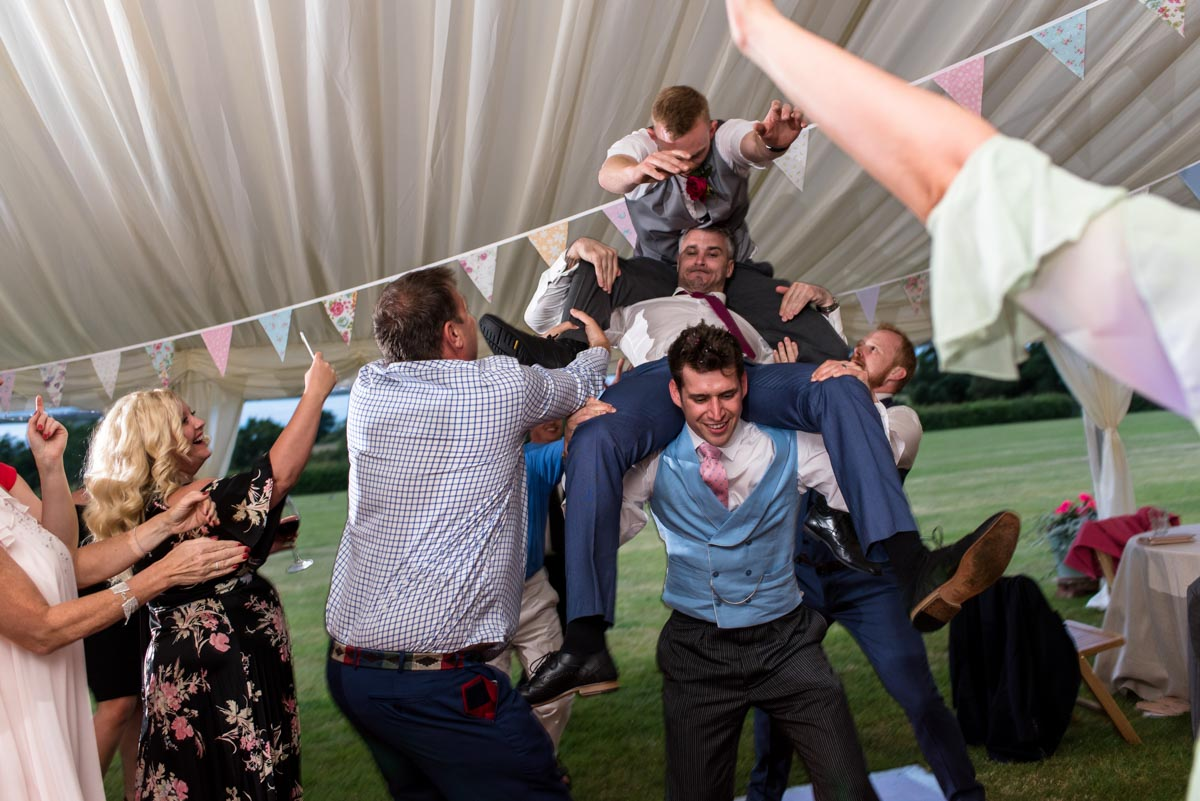 groom and friends messing about at Kent wedding marquee reception