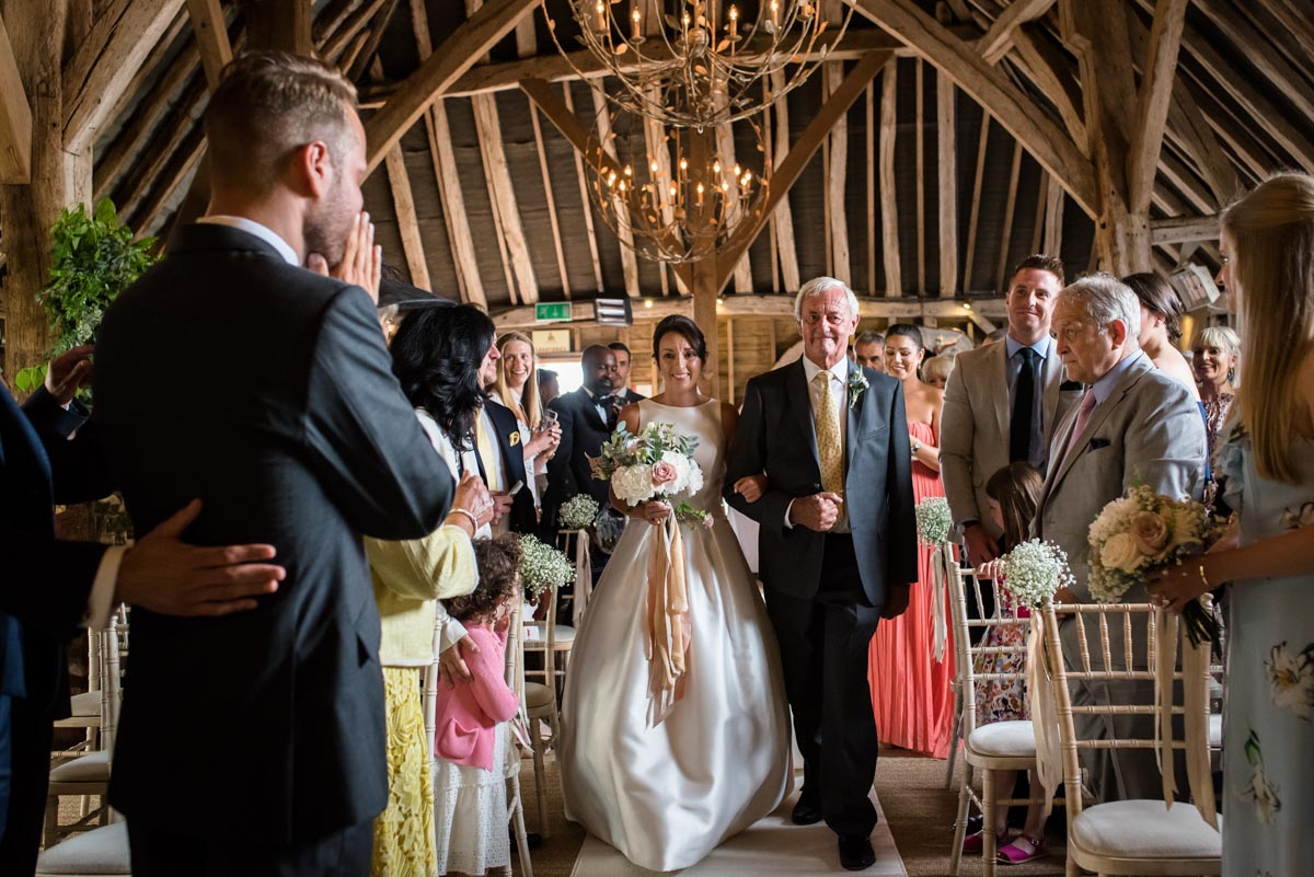 dad and bride walk down the aisle at Odo's Barn wedding in Kent