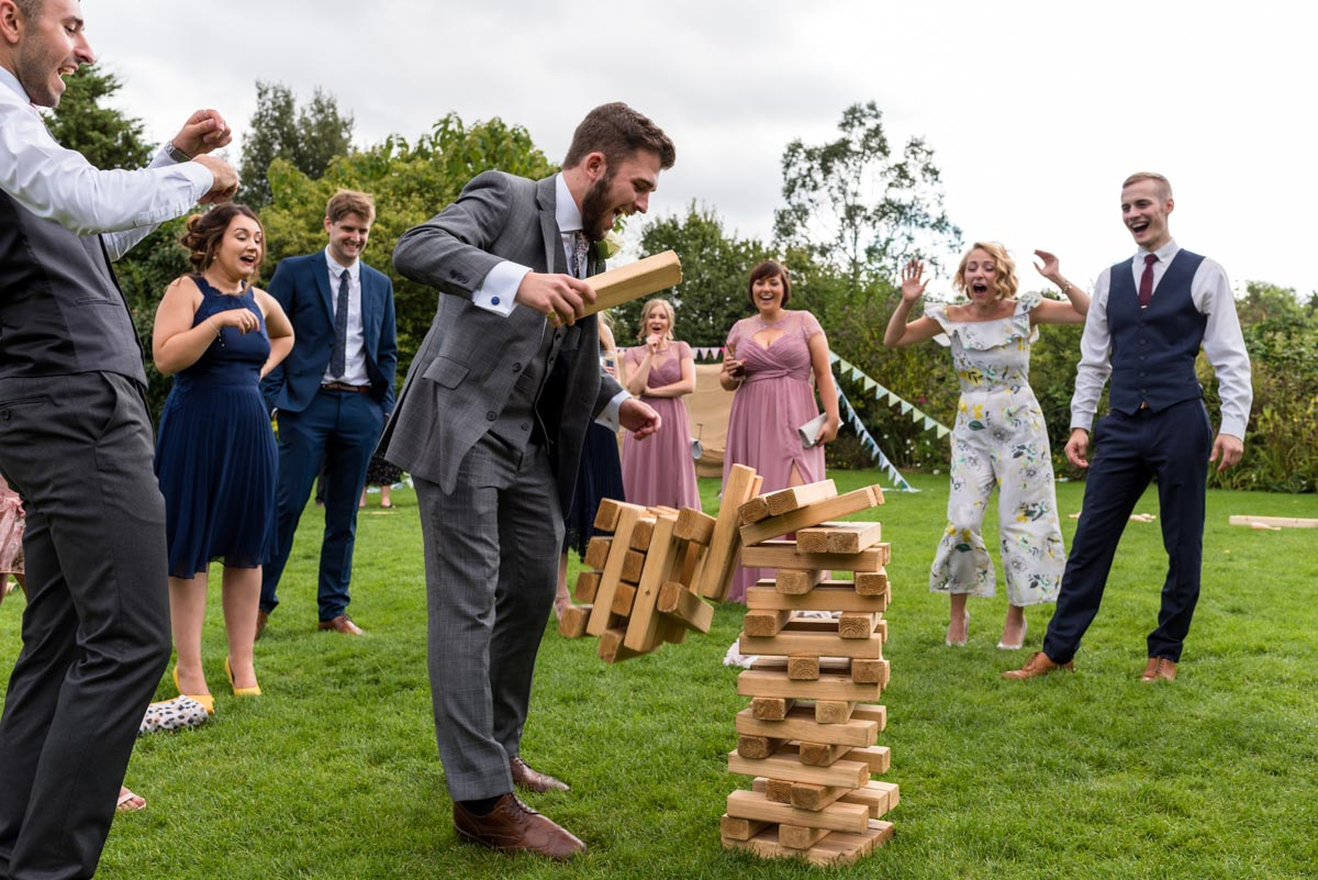 Wedding guests play giant jenga at The Gardens Yalding wedding