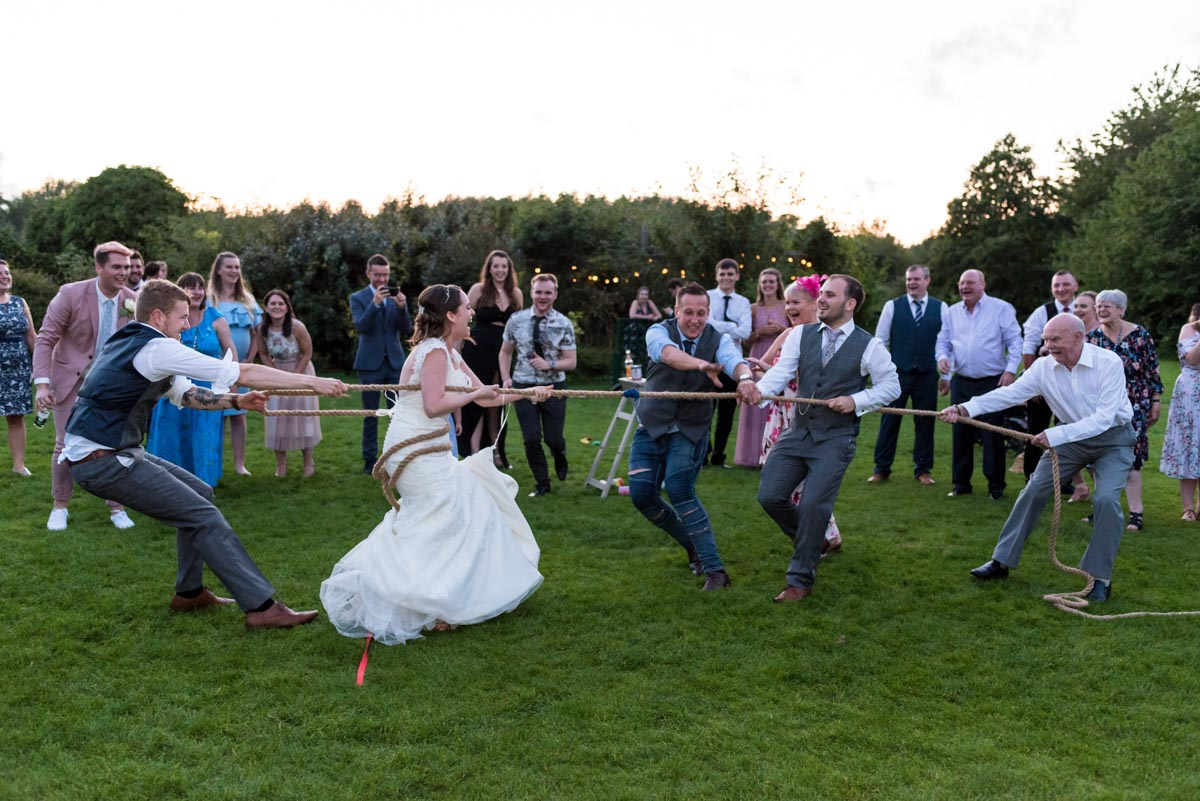 Bride and groom photographed playing tug of war at their Yalding Gardens wedding