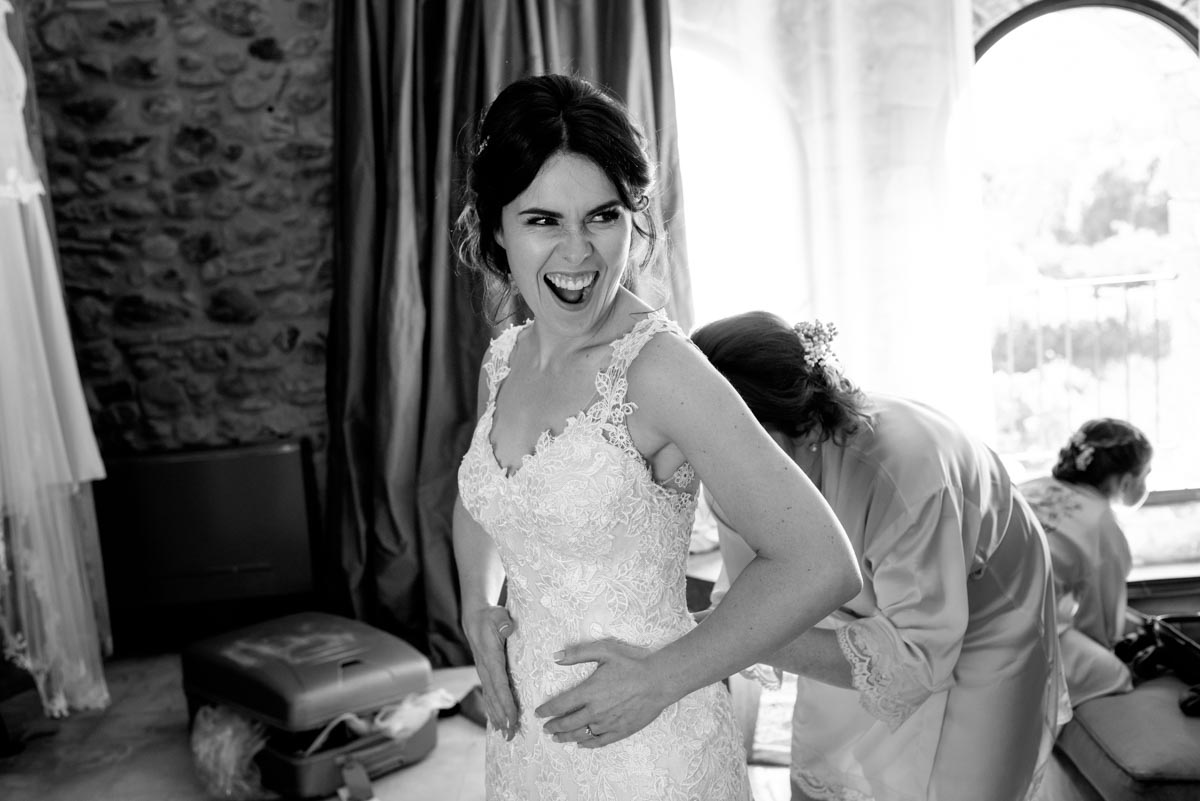 Photograph of a laughing Rebecca as she gets her dress on